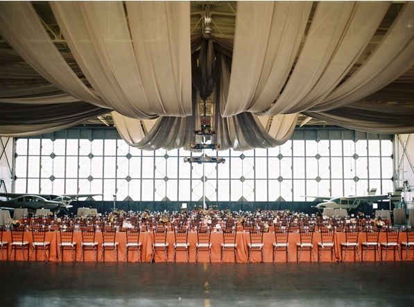 airplane-hanger-wedding-reception-venue-tables-centerpieces-flowers-decor-coral-beige