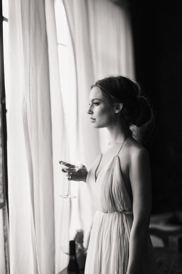 bride-standing-by-window-shot-soft-dress