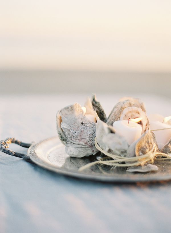 Table candle votives made from oyster shells.