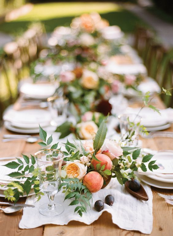 We adore a tablescape that feels both wild and refined. This organic setup of a rustic farm table with fruit laden centerpieces, a Linen Runner , and scattered figs evokes a sense of carefree summer elegance. You can recreate this look by adding wooden bowls of fruit along with centerpieces down the center of your family-style dinner tables.