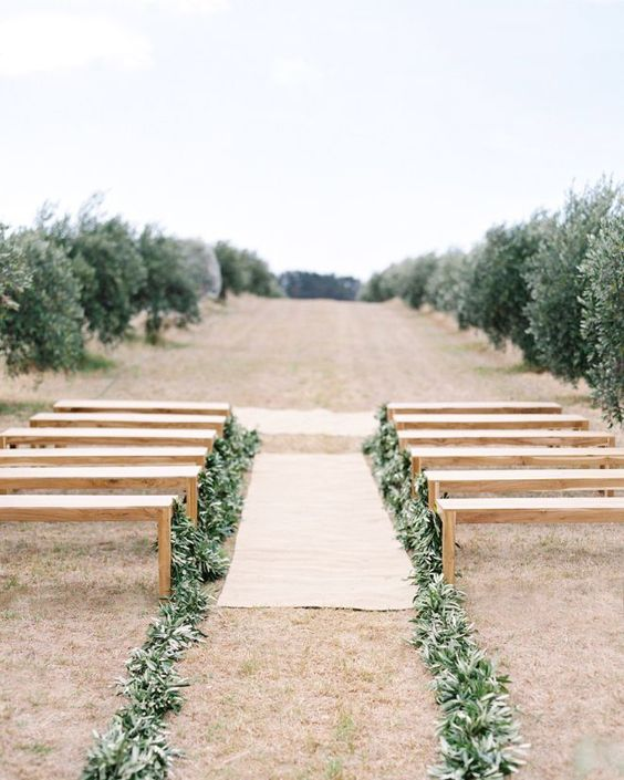 Sometimes a simple garland can change your entire ceremony look. Here the couple lined the wooden benches with olive branch garlands to match the surrounding olive grove. We love how the space is instantly transformed from simple to special with this little green addition.