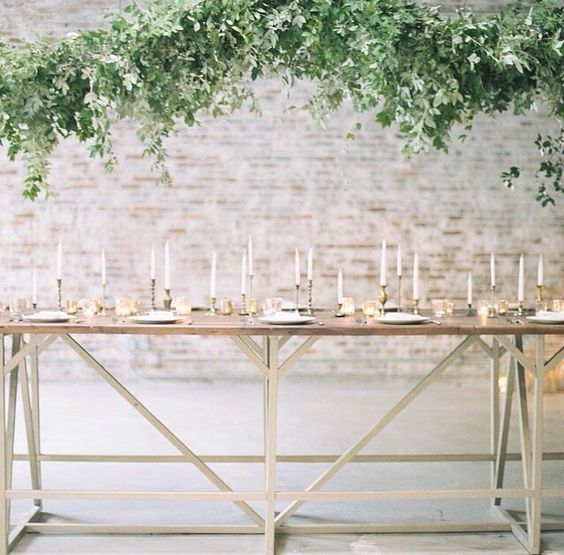 Perhaps a garland of mixed greens draped from the ceiling? The effortless and lush look of this garland is exactly the kind of addition we love. Keeping the table décor to a minimum with scattered candles like these, adds emphasis on the gorgeous garland above.