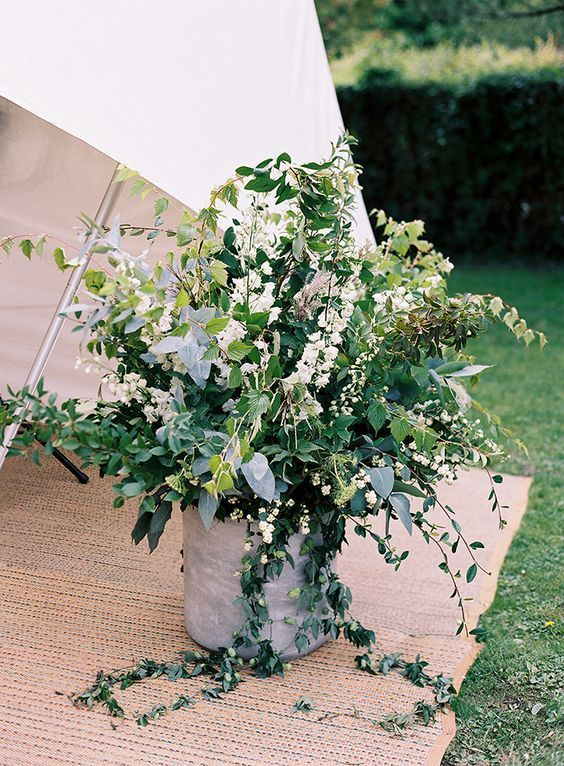 Adding wild and textured arrangements of greens throughout the wedding is also a fun way to continue your green theme, especially if the greens are foraged from the venue itself. Have the greens arranged in cement pots for an added organic look.