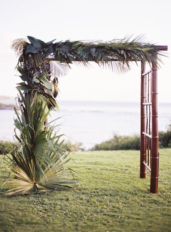 A tropical arch made from a simple bamboo frame and lush tropical palms is our favorite ceremony look. We love how the dark wood adds elegance and the monochromatic leaves help the focus shift on the texture of the foliage. We can imagine guests seated on dark-stained benches and the aisle lined with additional palm leaves.