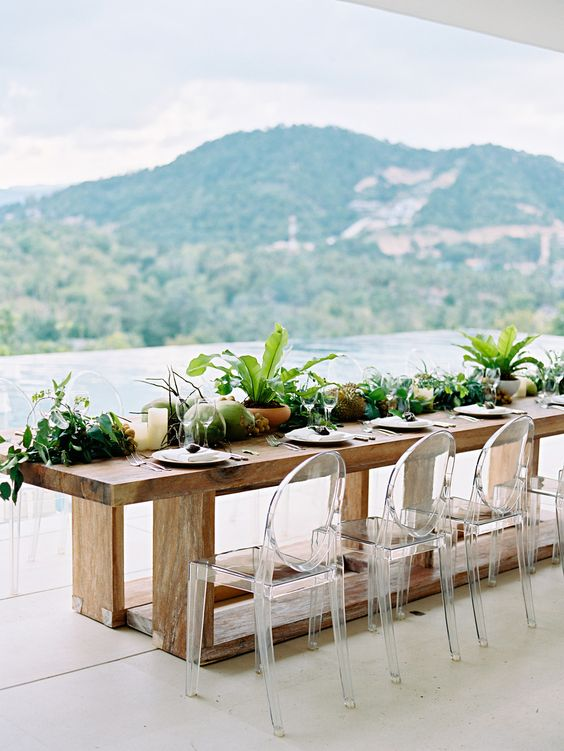 A beautiful runner of local fruit, foraged foliage, and potted plants is the perfect solution to a beach wedding centerpiece. These simple components perfectly complement the wooden table and the stunning backdrop of the bay. Clear leucite chairs add a modern touch to the overall feel. We love this look for its refined and focused attention.