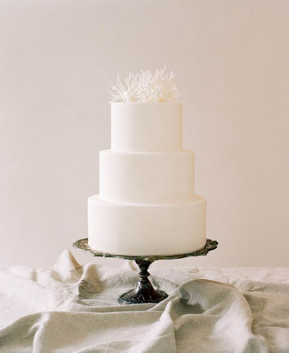 A simple, three-tiered wedding cake is instantly transformed with a coral topper made of royal icing. The neutral color palette lends a hand in making this cake a classic beauty. Use a beautifully tarnished silver cake stand like the one pictured or opt for a wooden stand instead.