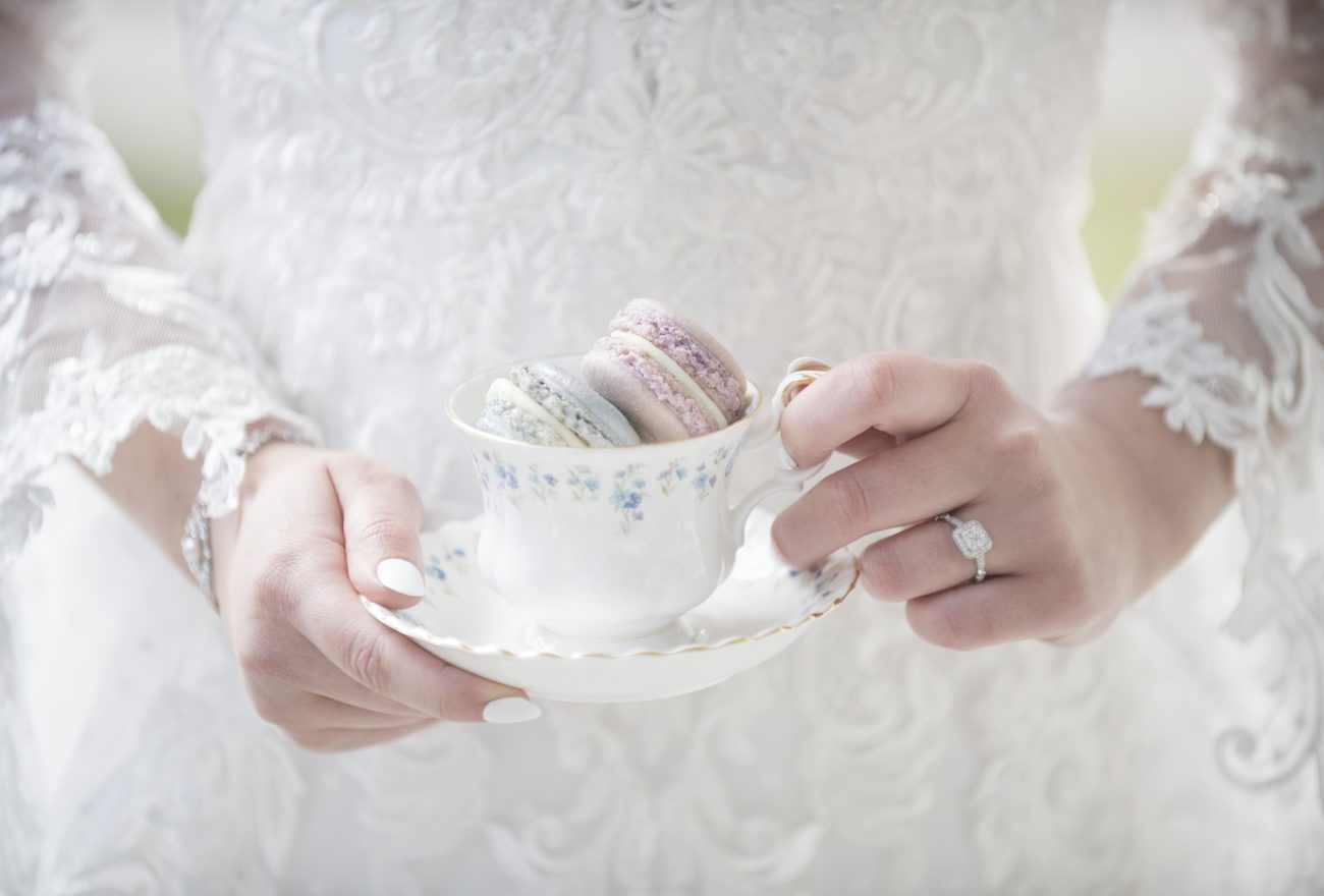 bride holding teacup with macaroons