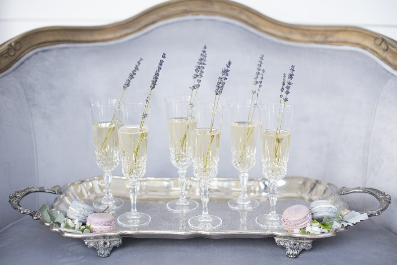 champagne glasses on a silver tray with lavener