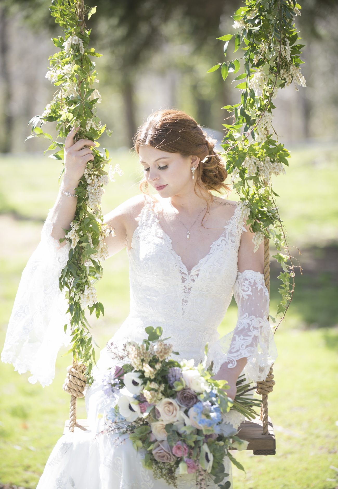 Bride sitting on floral wrapped tree swing