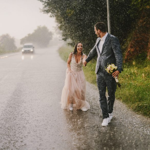 Just married couple holding hands and walking on rain. Walking in wet ceremonial clothes on drive road. Smiling and having fun.