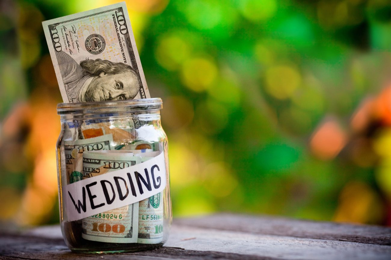 Glass jar with dollars and the word wedding paper label.The concept of saving money for a wedding.