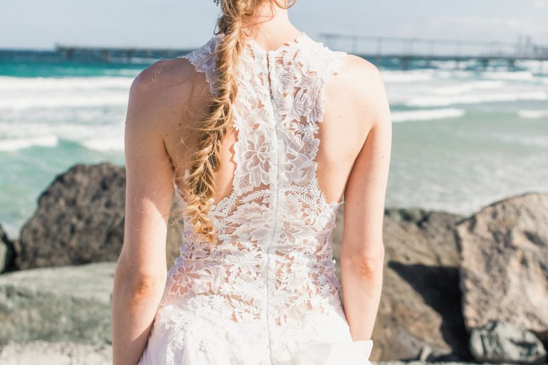 Bride wearing wedding gown at beach