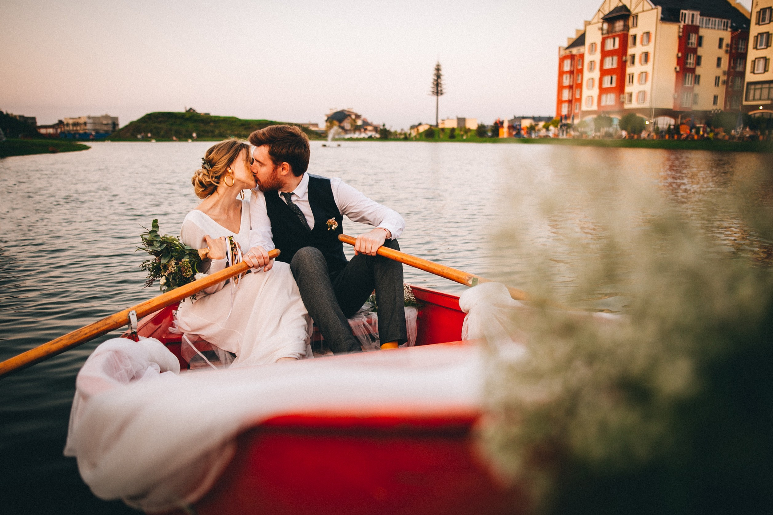 Bride and groom kissing on a rowboat