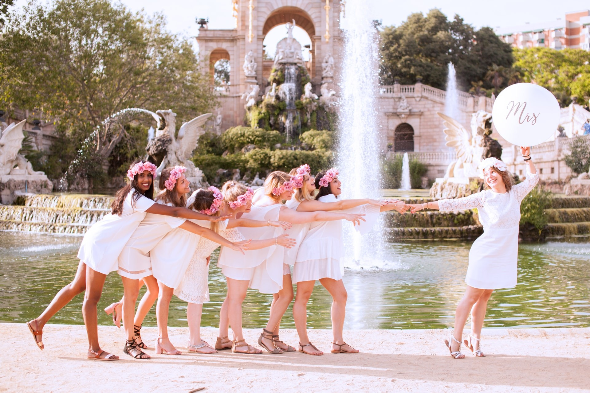 Bride and bridesmaid group photo in front of fountain