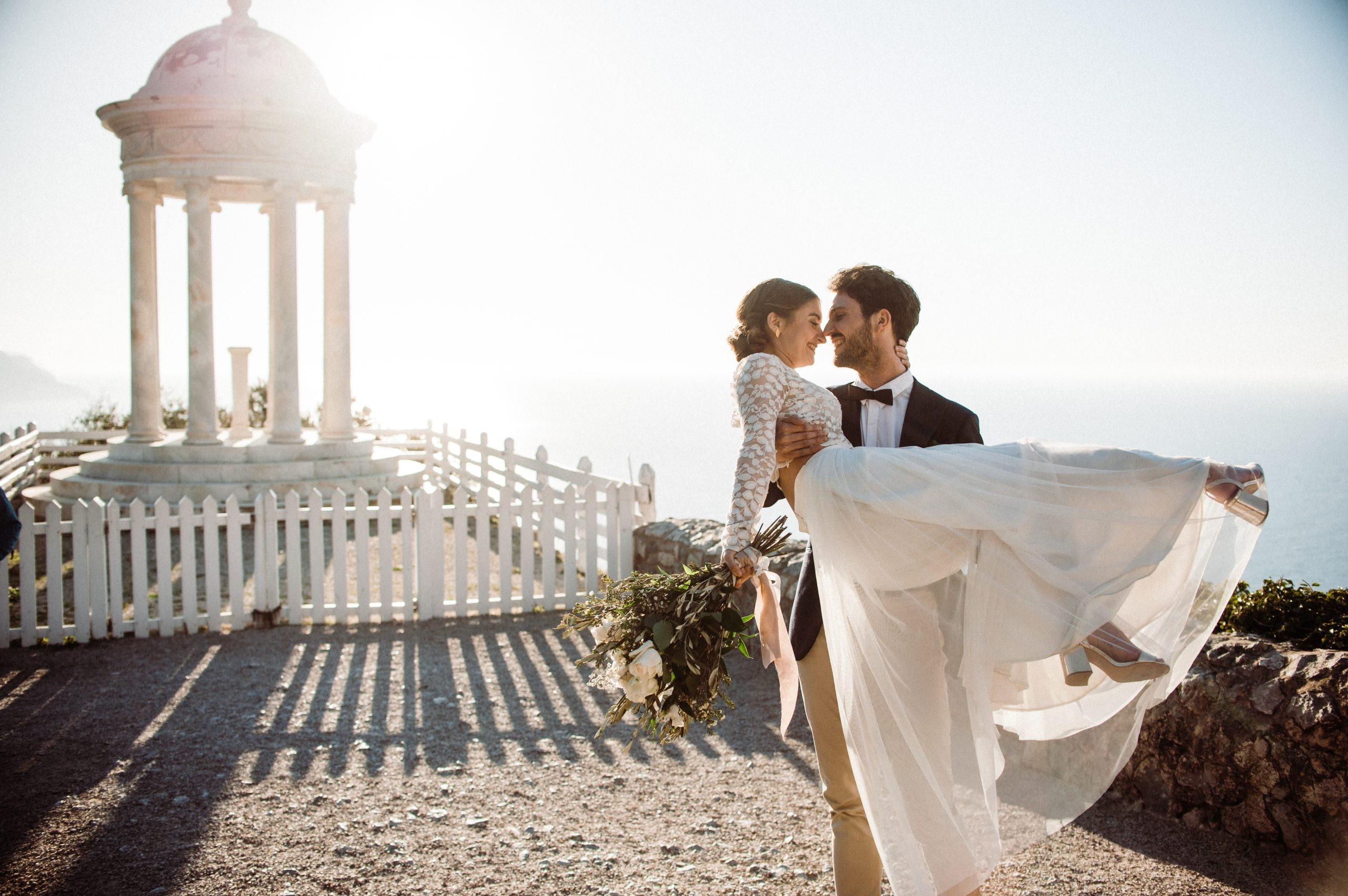 Groom holding bride in romantic destination wedding on a Spanish Island
