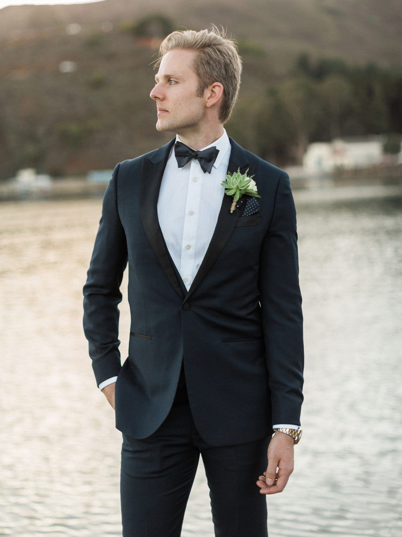 Groom wearing a suit and posing in front of a lake