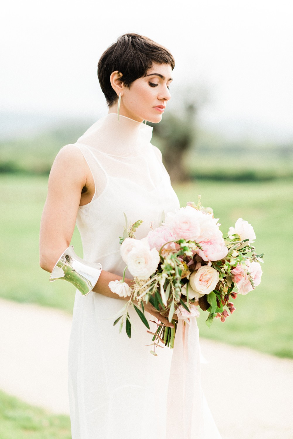 Short haired bride holding a bouquet of flowers