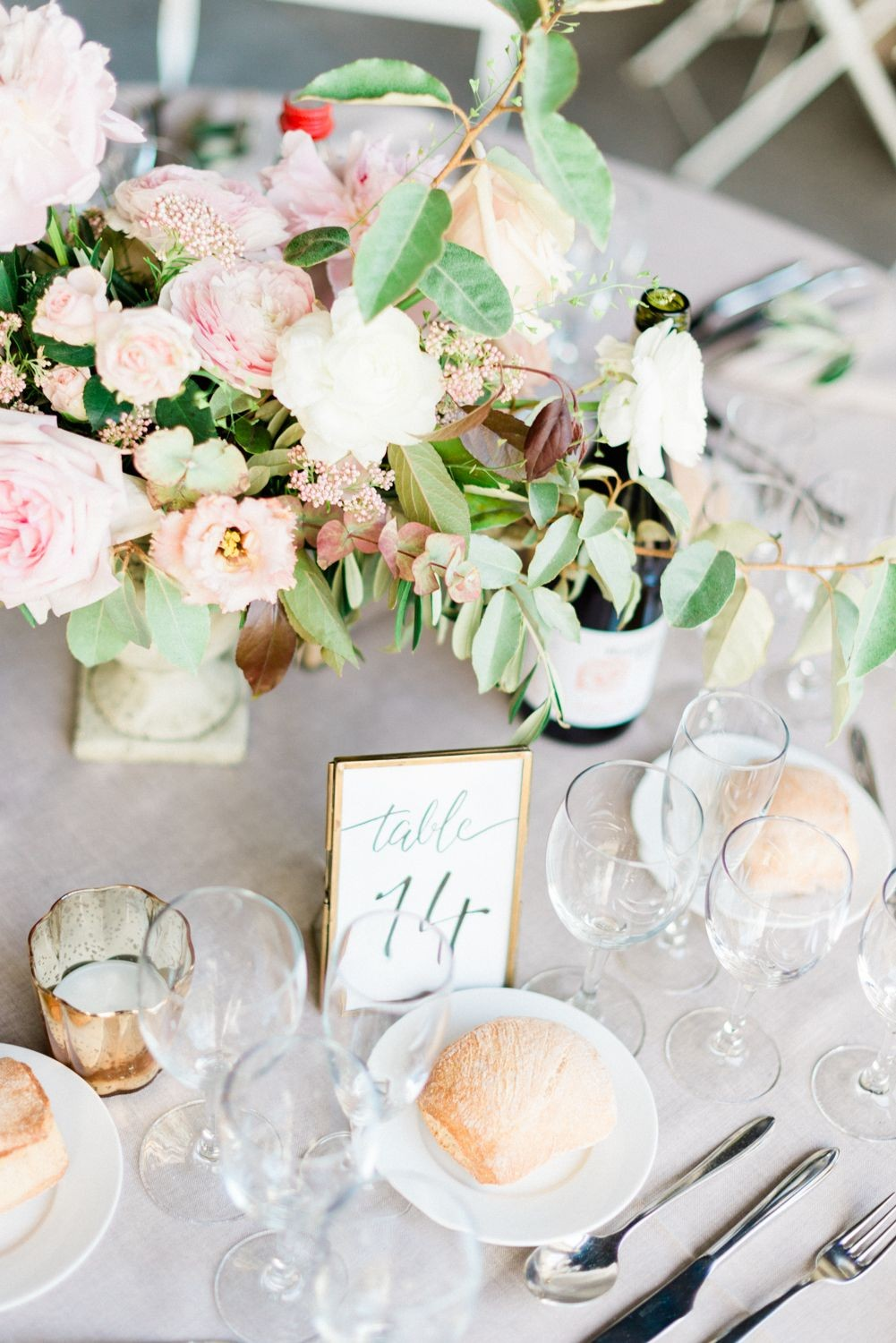 Flower bouquet and wine glasses on dinner table